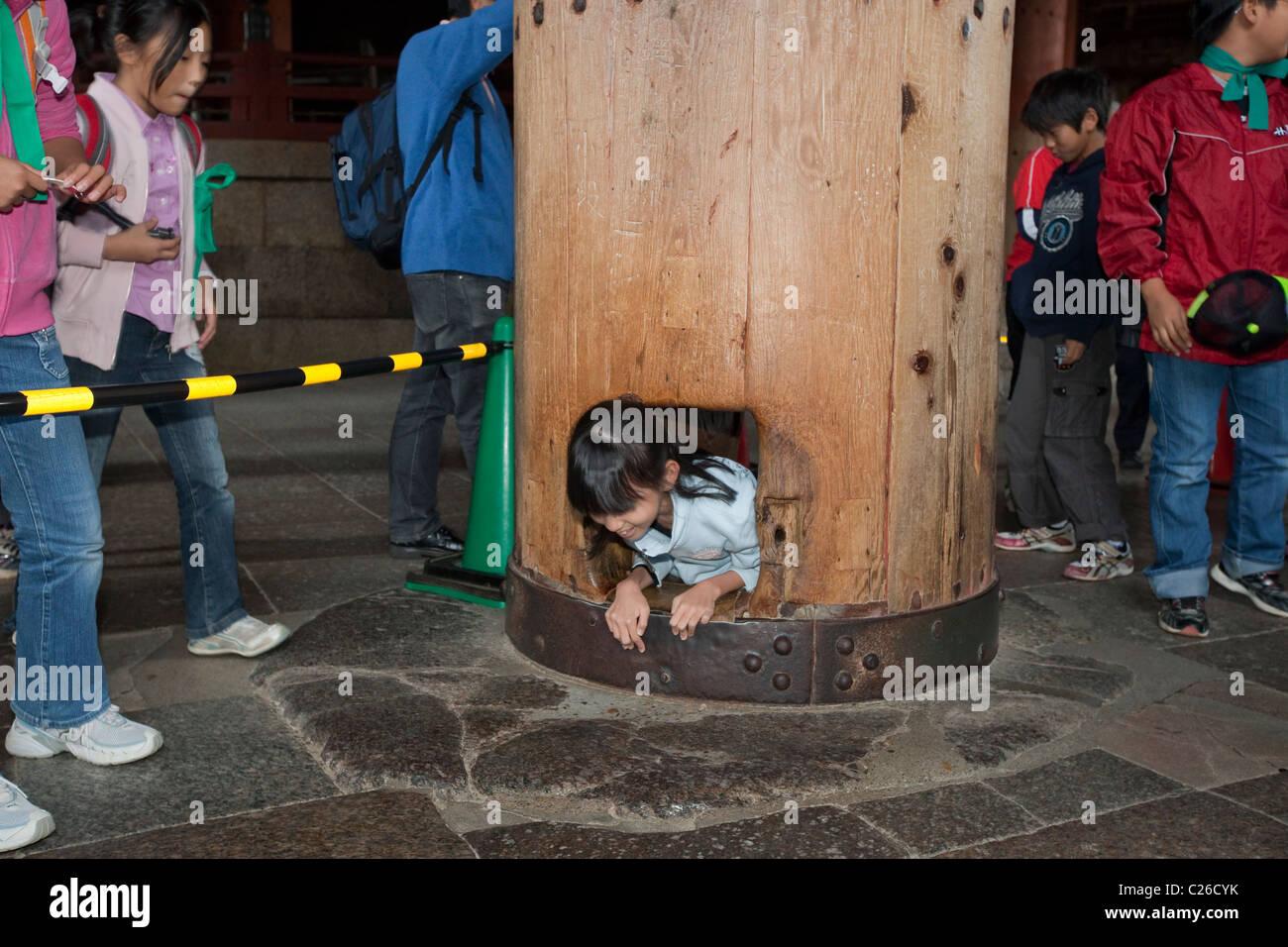 Schoolgirl squeezing through hole in wooden column in Daibutsu-den Hall at Todai-ji Temple, Nara, Japan. - Stock Image