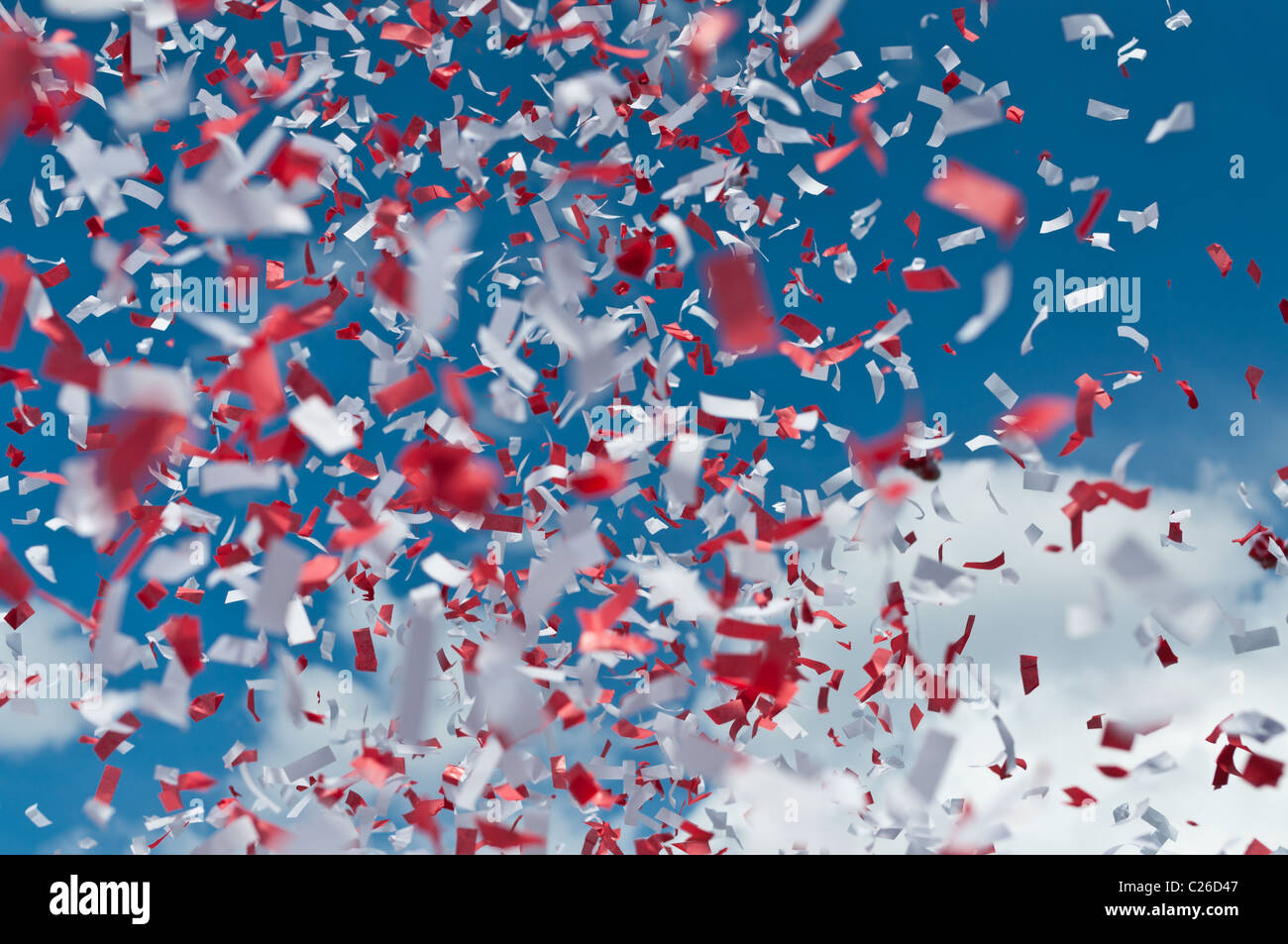 Red and white strips of paper confetti fill the air with a blue sky and white clouds in the background. - Stock Image