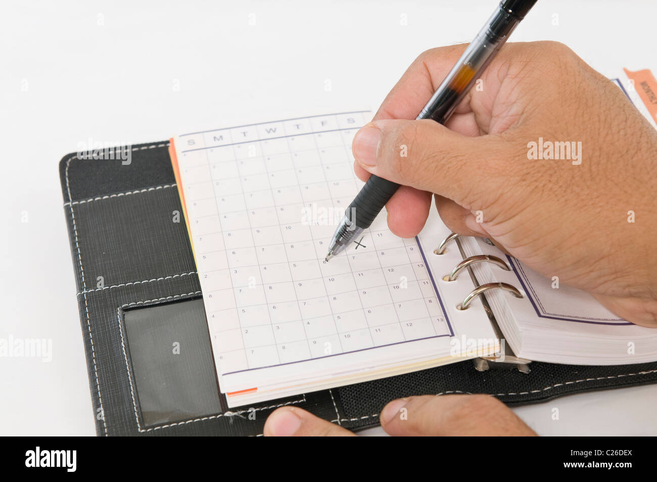 Hands holding a pen while marking the calender - Stock Image