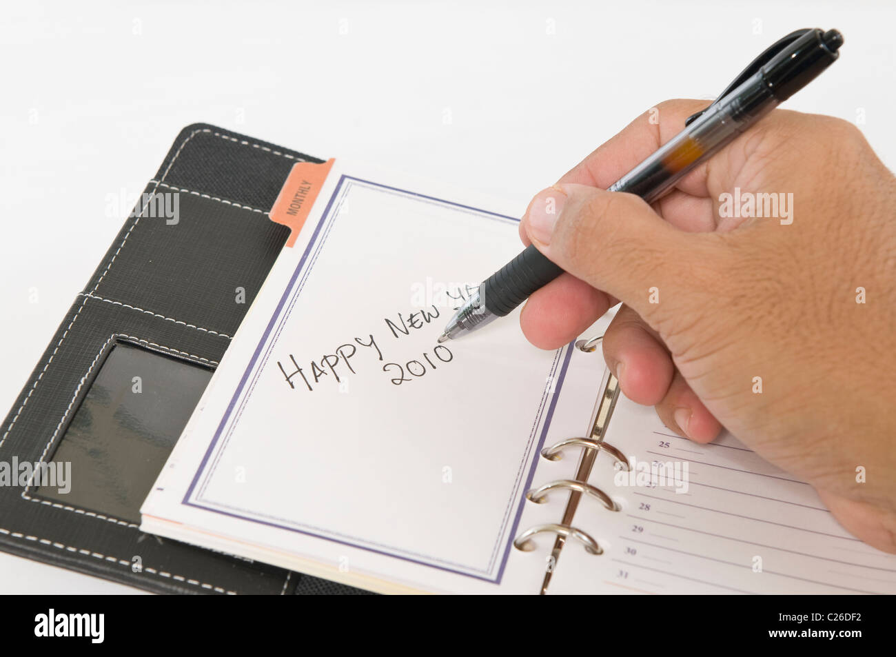 Hands holding a pen while writing Happy New Year - Stock Image