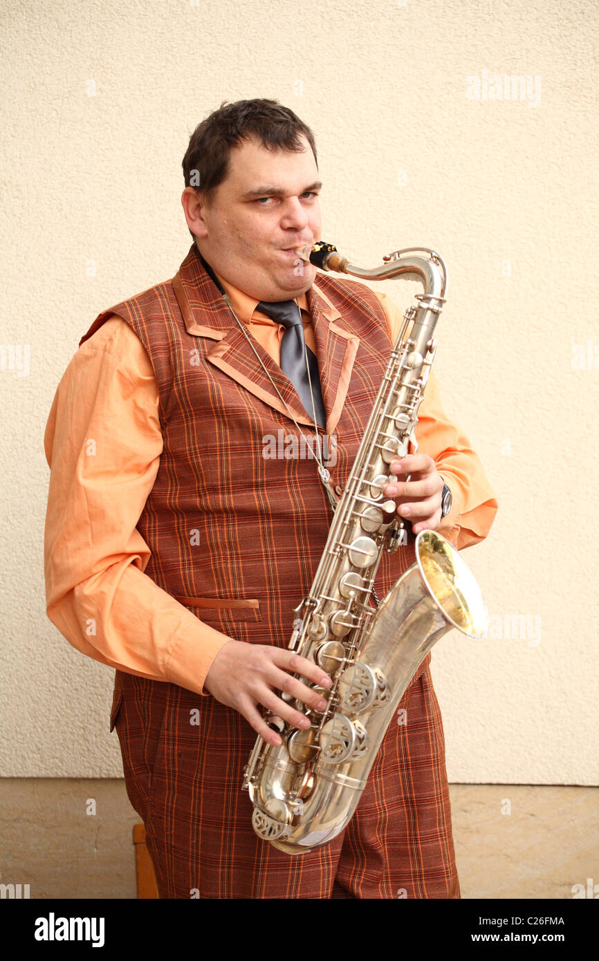 Musician from the old time band Funny Fellows playing on the saxophone. - Stock Image