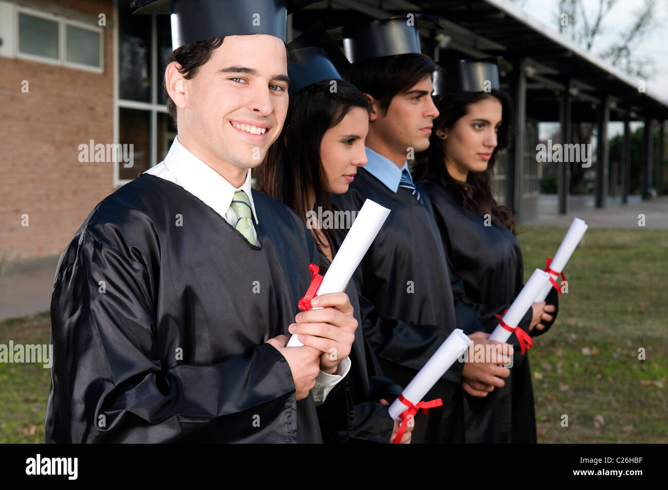Four, students, schoolmates, smile, smiling, looking, at, the, camera, getting, a, diploma, at, graduation, at, - Stock Image