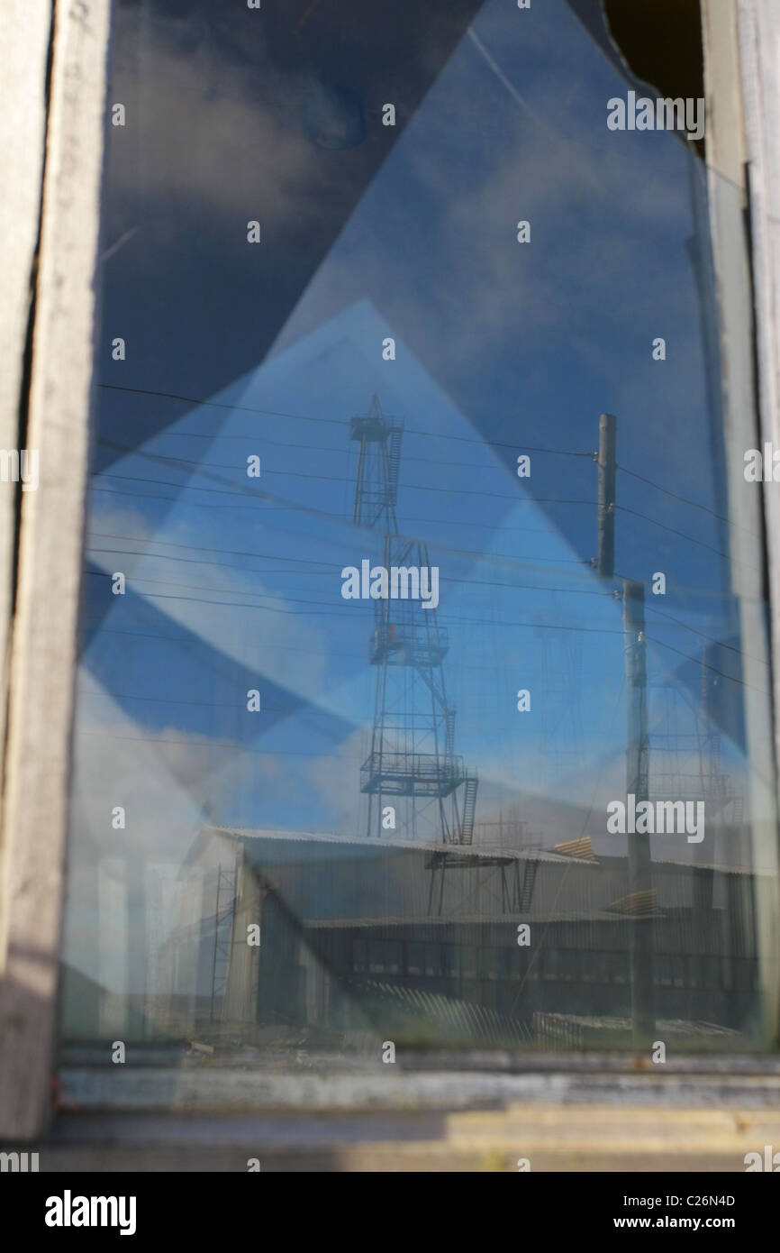 Derrick is reflected in a broken window. Yamal peninsula, RUSSIA - Stock Image