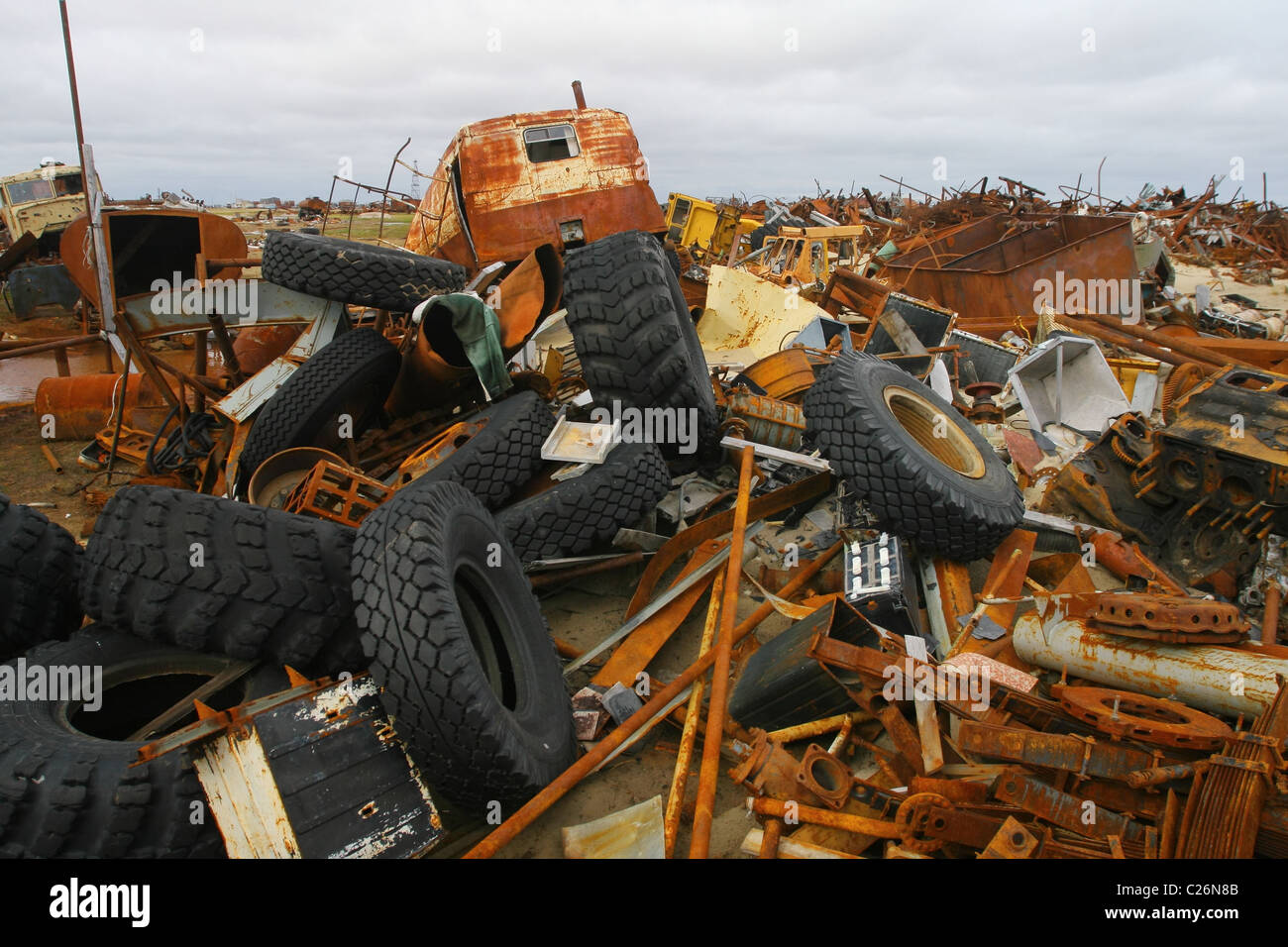 Rusty metal, heavy tires and so on occupy the frame space to the horizon. Yamal peninsula, RUSSIA - Stock Image