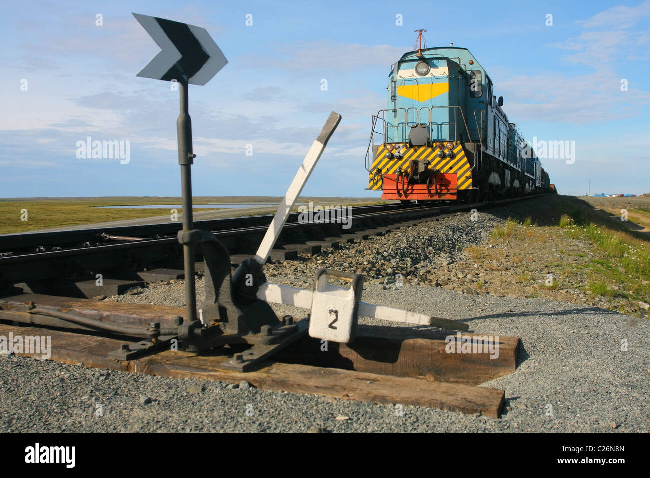 Locomotive is moving south along the road Obskaya-Bovanenkovo passing crossing loop Hralov. Yamal peninsula, RUSSIA - Stock Image