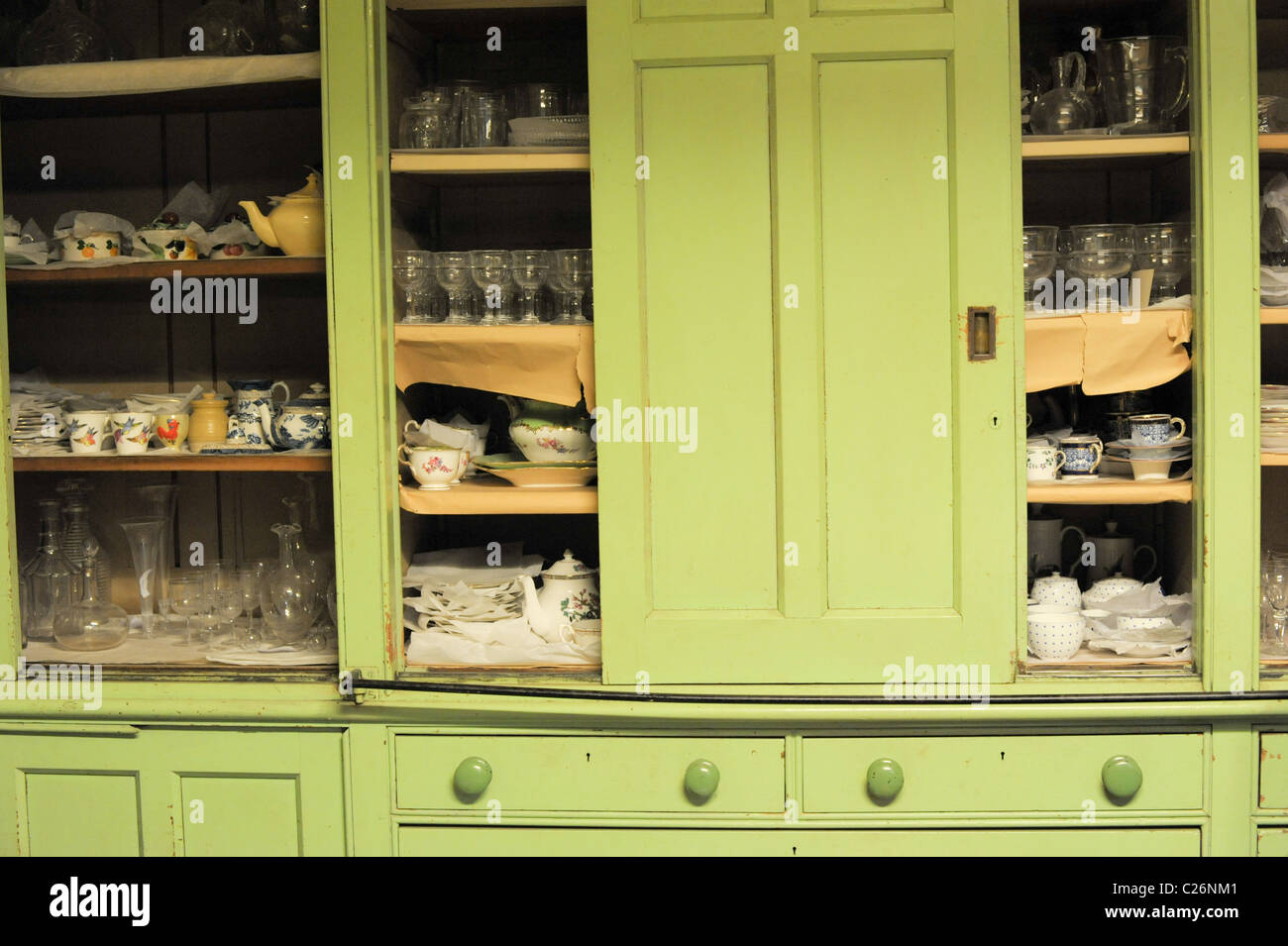 Bright green English country house Victorian kitchen cupboards full of collectable old crockery, china, glasses - Stock Image