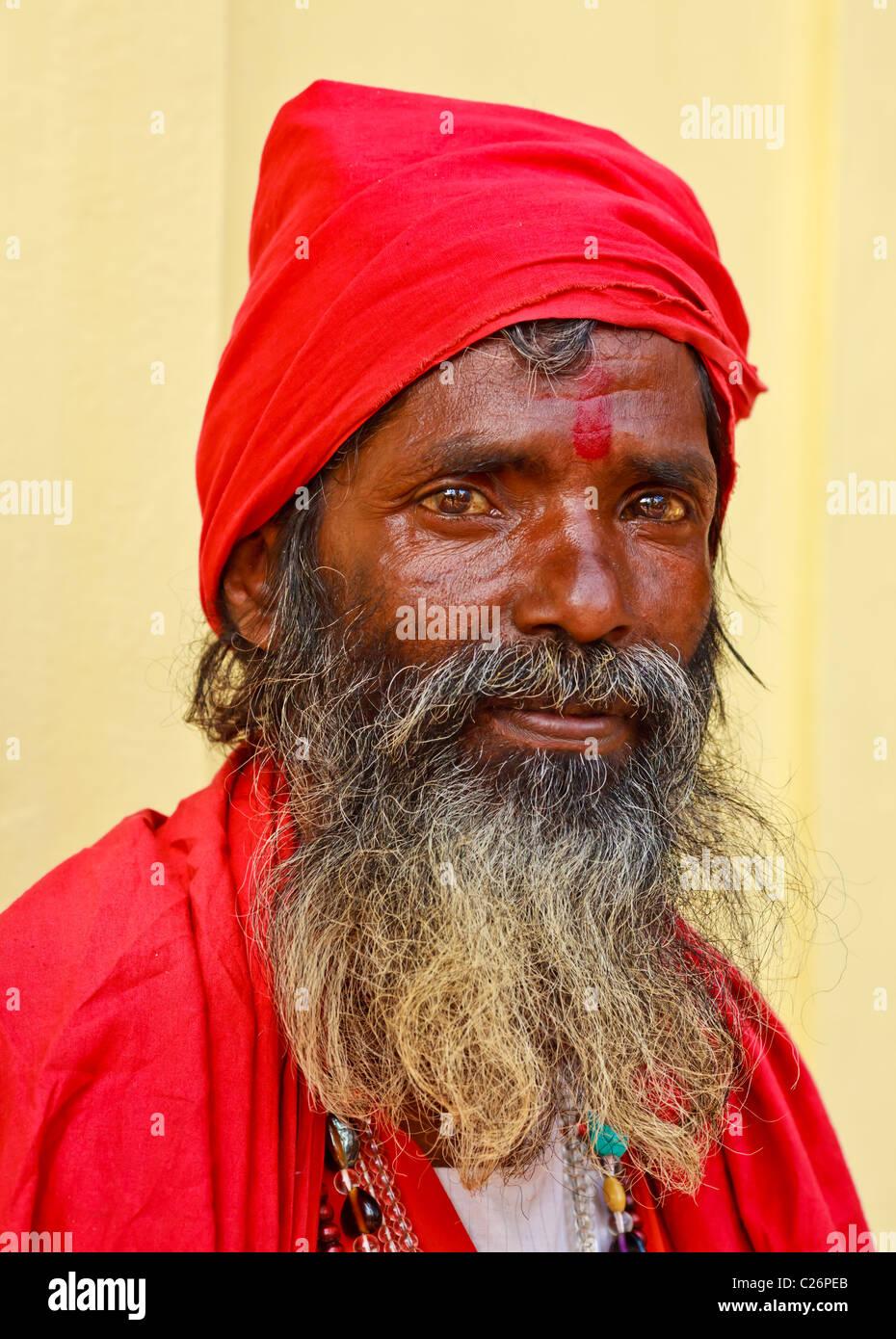 Portrait of elderly sadhu dressed in red clothes, Kamakhya Temple, Guwahati, India - Stock Image