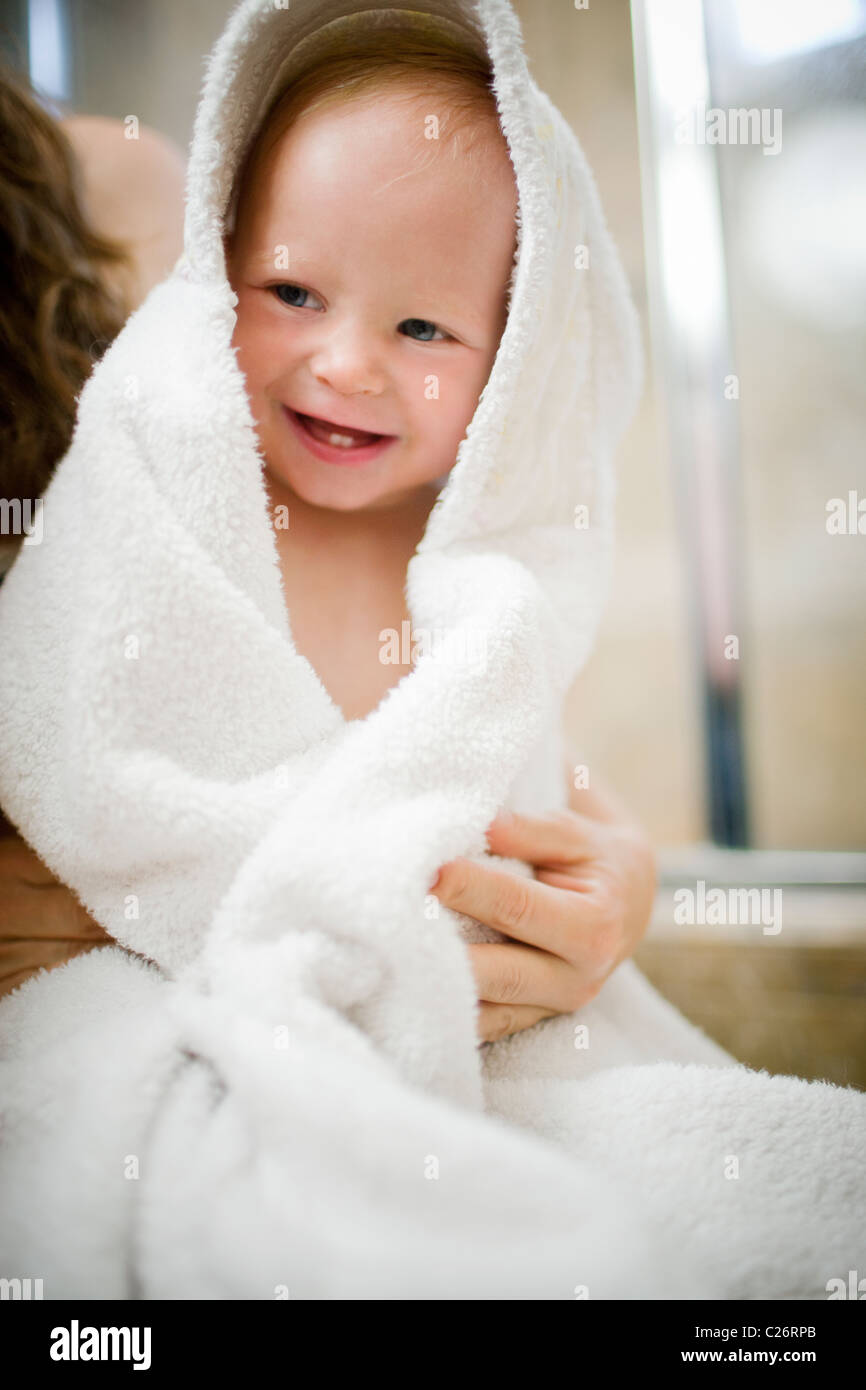 Mother drying off 1 year old baby girl after bath - Stock Image