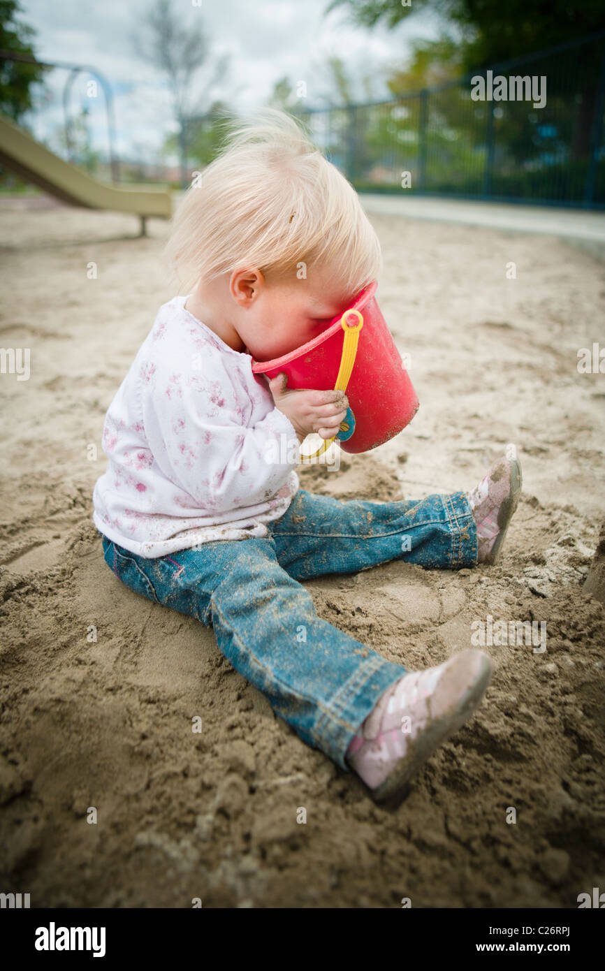 1 Year old girl in Playground Sandbox Playing with Sand Toy - Stock Image