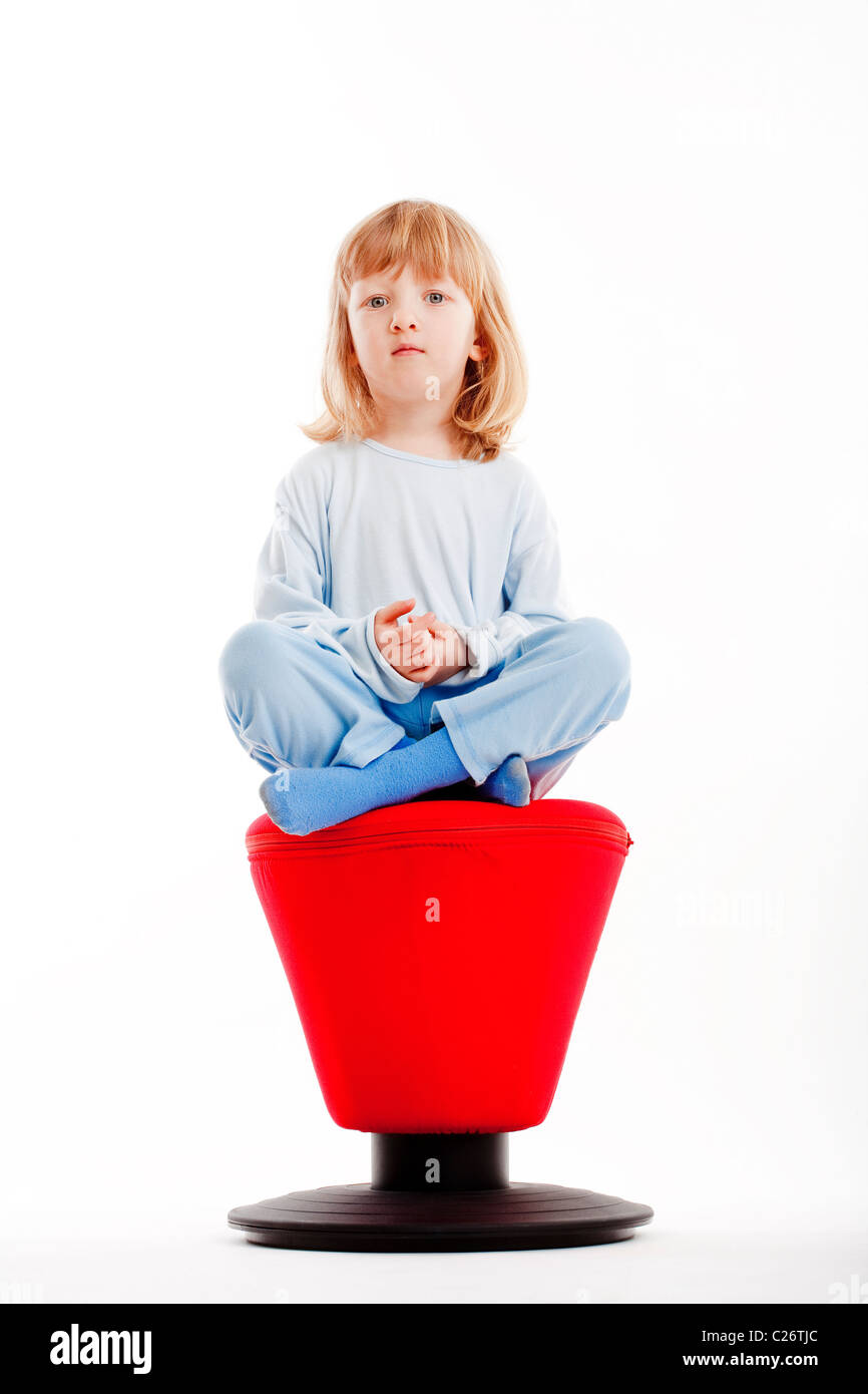 boy with long blond hair sitting on a red stool - isolated on white - Stock Image