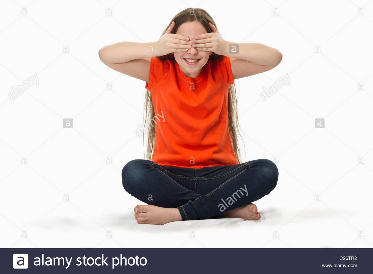 close-up of a 10 year old girl with hands covering eyes playing hide and seek - Stock Image