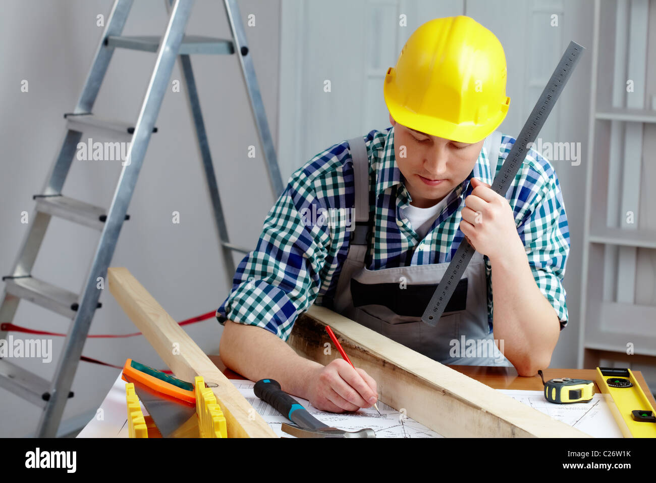 A young repairmen sitting at table and working with a plan Stock Photo