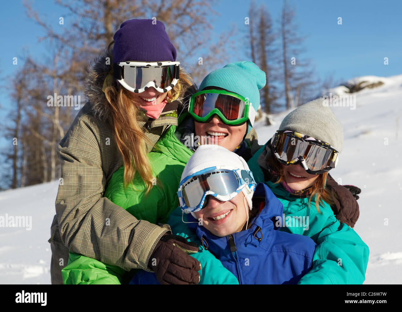 Portrait of four young people in ski goggles embracing - Stock Image