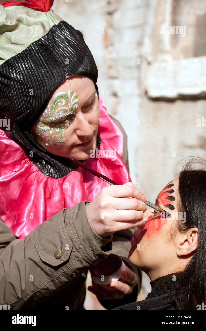 A young woman having her face painted, Venice, Italy - Stock Image
