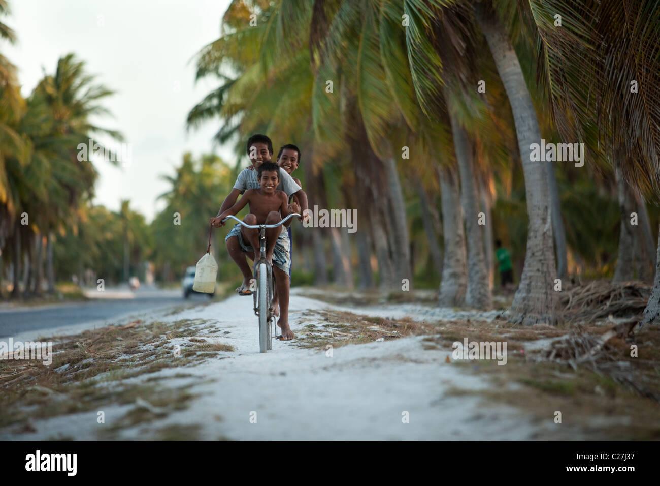 Kiritimati, Kiribati, Christmas Island, three island boys having fun all riding one bike - Stock Image