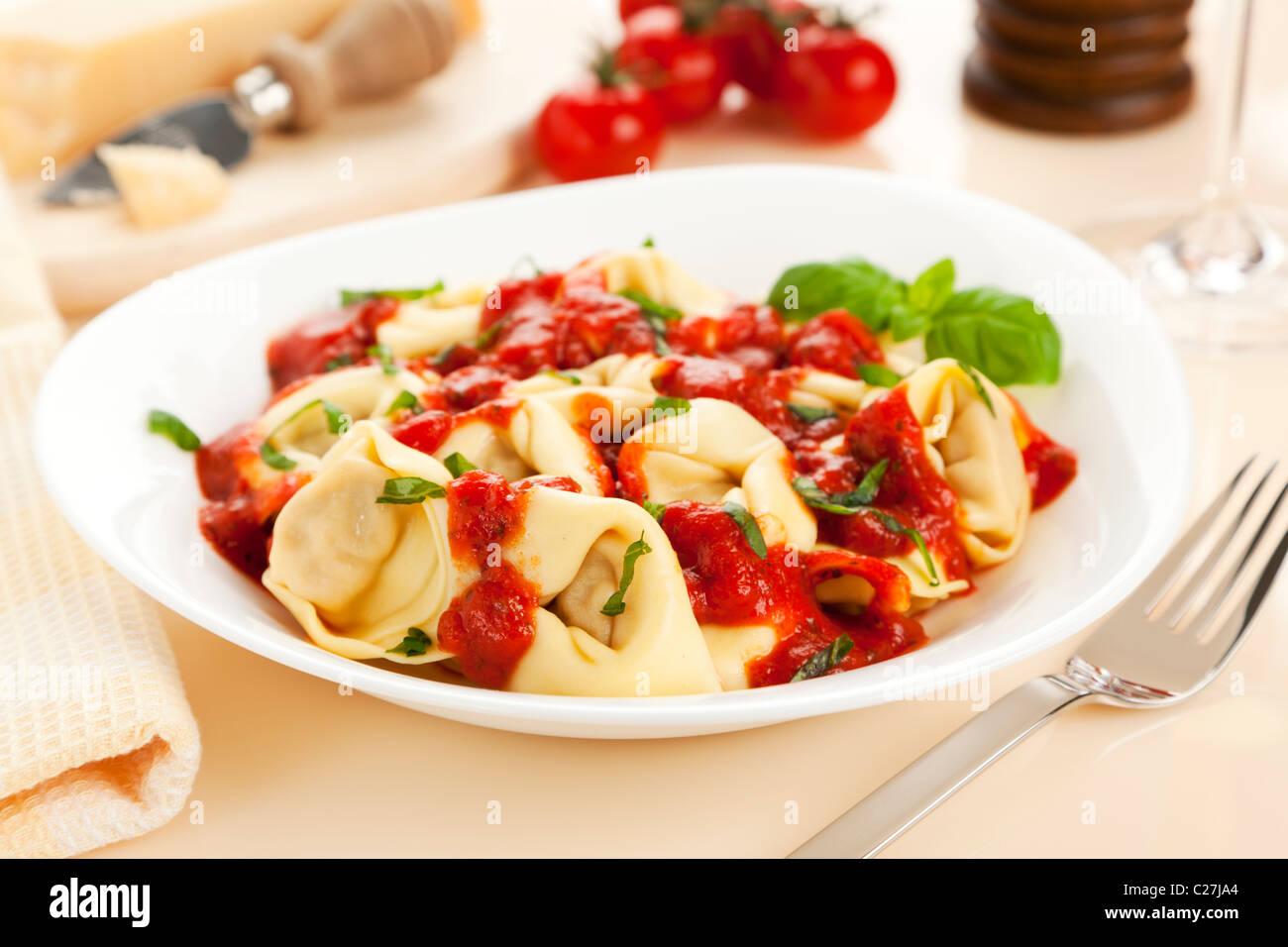 tortelloni pasta with tomato sauce and fresh basil Stock Photo