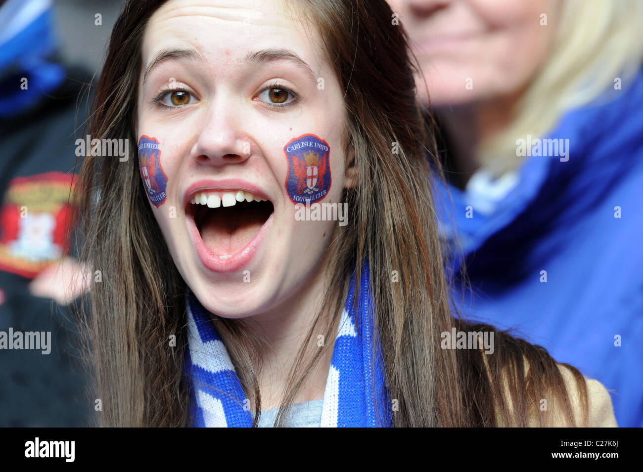 Attractive female football supporter wearing Carlisle United club badge transfers on her face - Stock Image