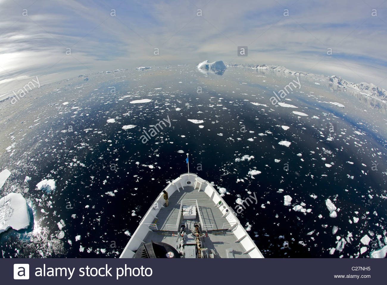 National Geographic Endeavor cruises through sea ice and past icebergs. - Stock Image