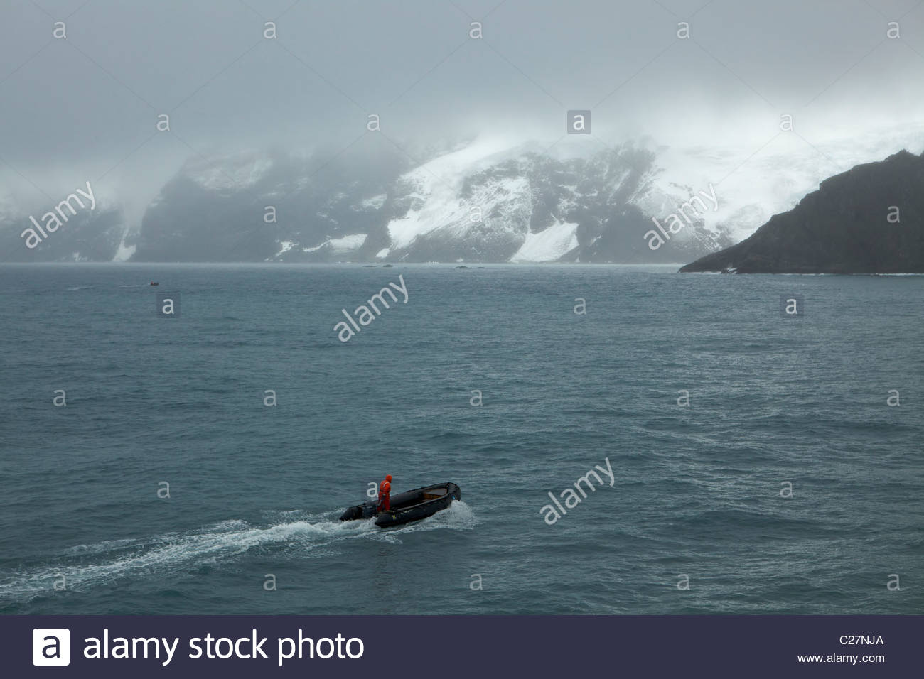 A man in an inflatable boat off of the coast of Elephant Island. - Stock Image
