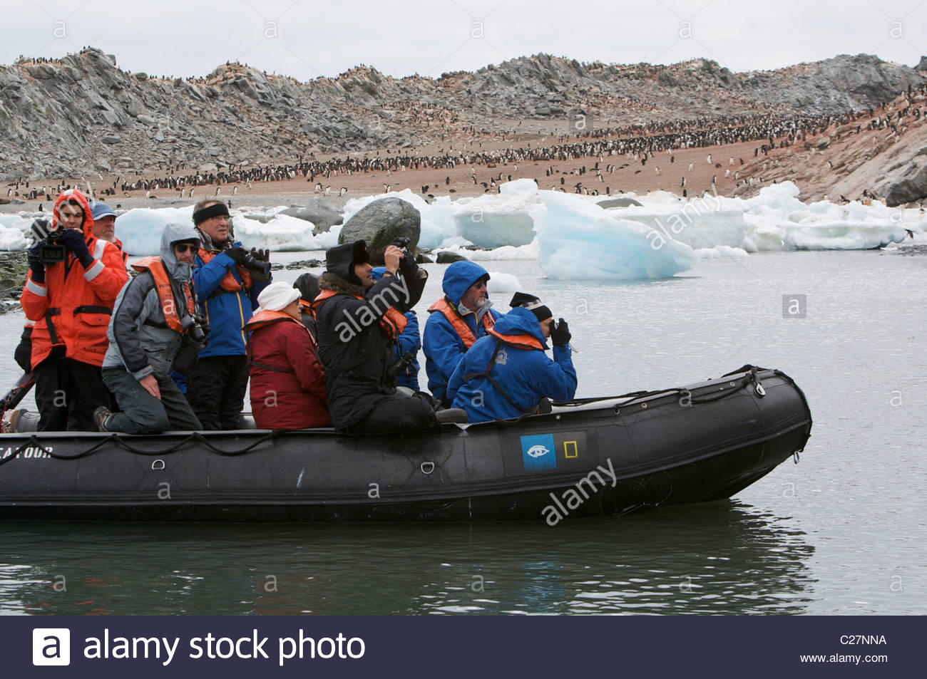 Inflatable boat tour at Heroina Island adelie penguin colony. - Stock Image