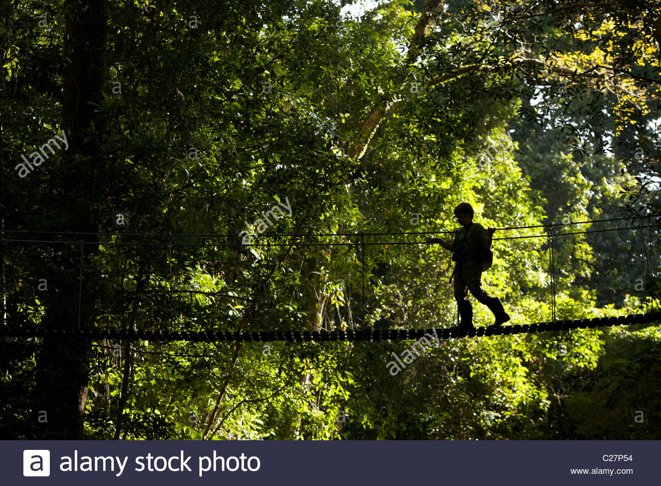 A boy crossing a suspended bridge over a river. - Stock Image