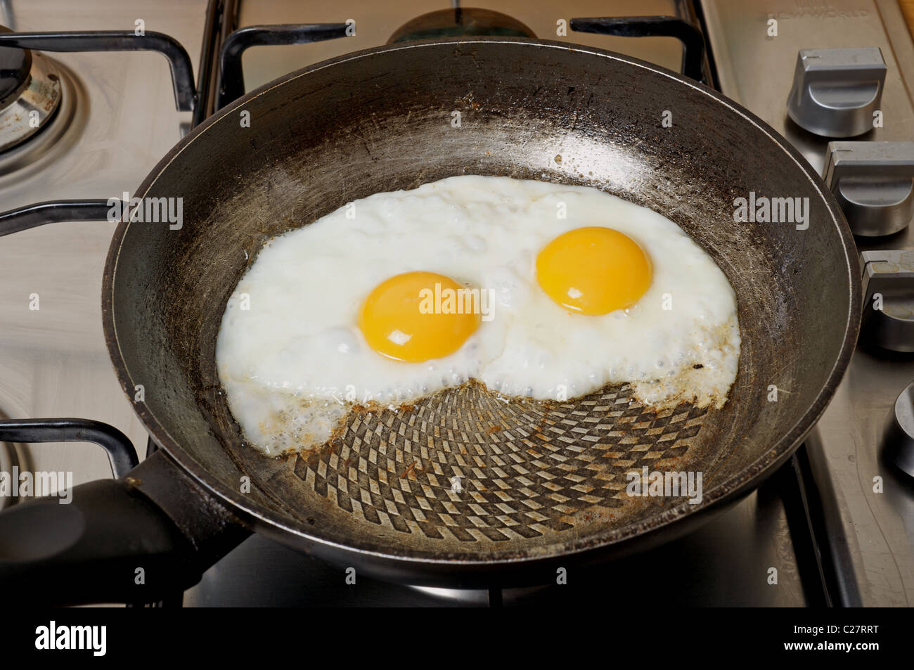 Fried organic egg cooking in frying pan - Stock Image