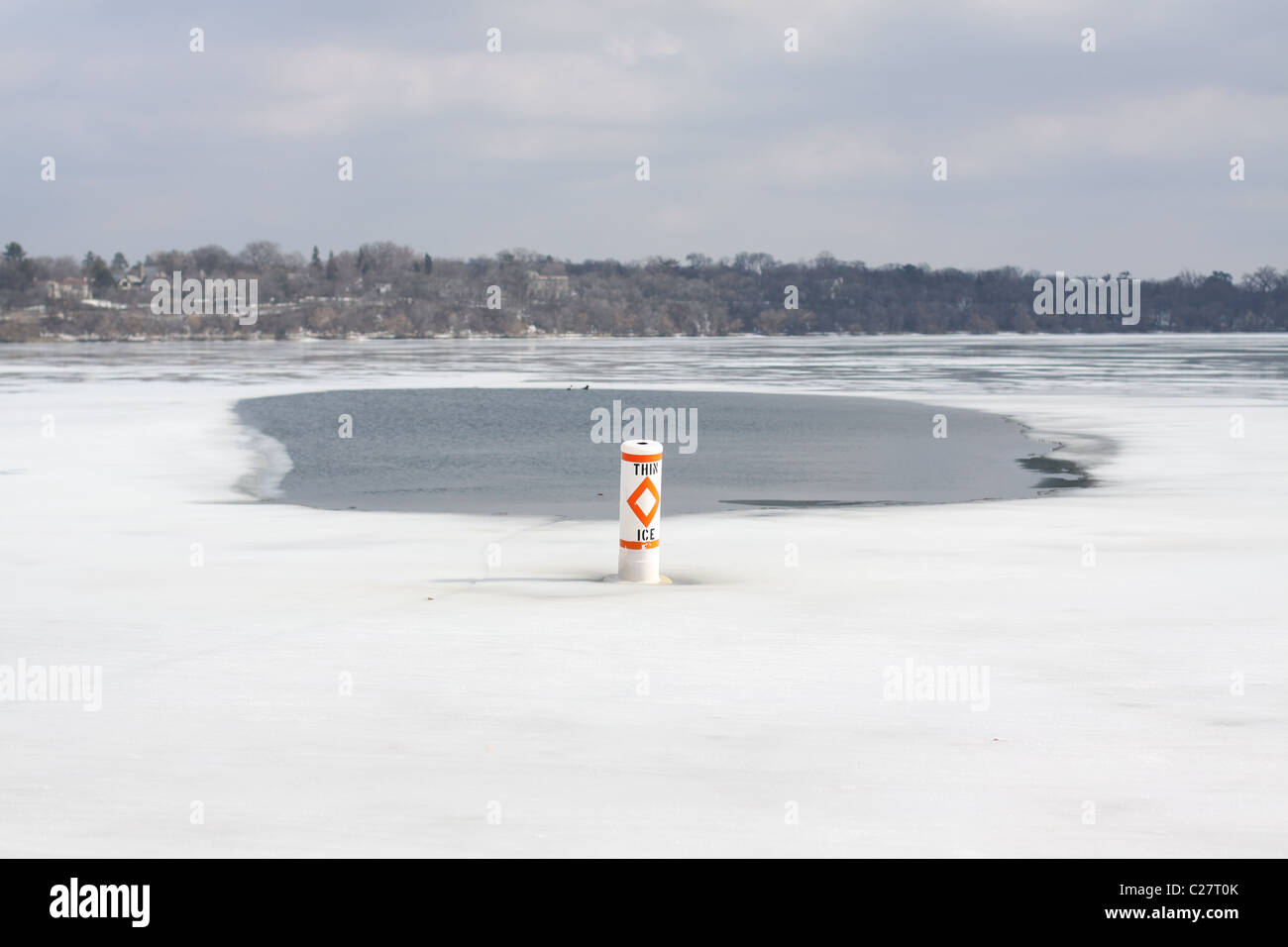 A lake thawing in early spring, with a 'thin ice' sign. - Stock Image