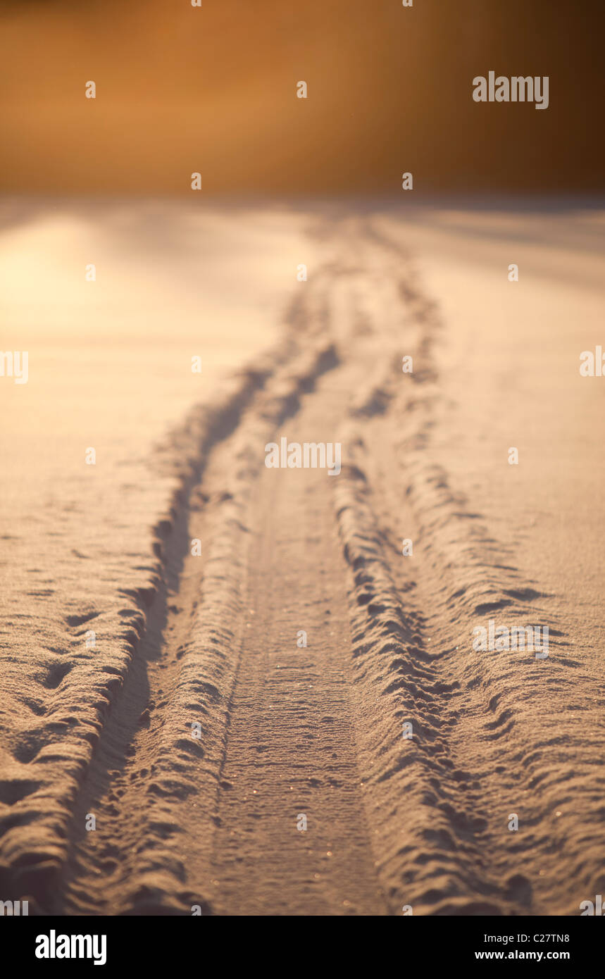 Snowmobile tracks on snow at Winter - Stock Image