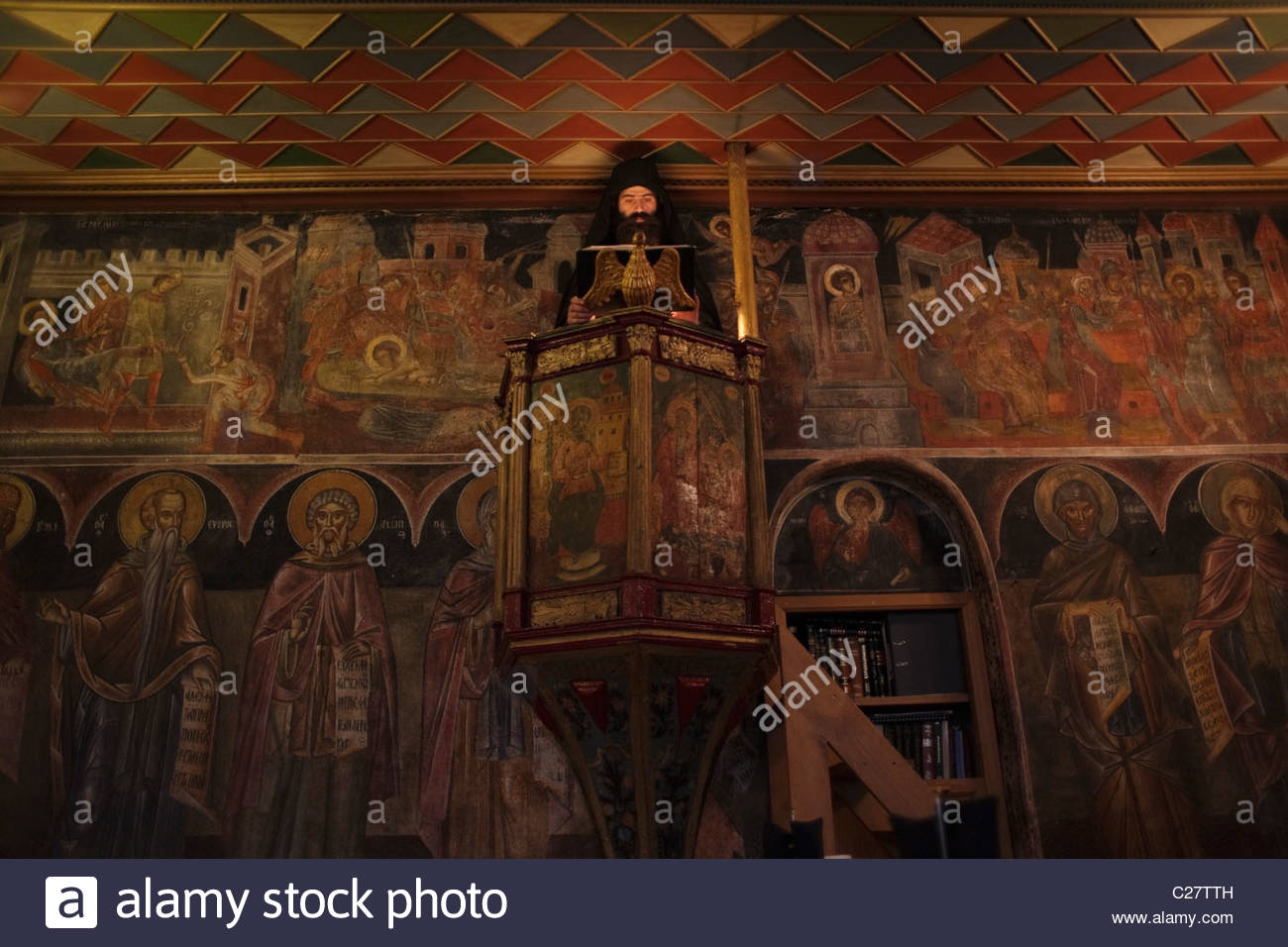 A monk reads the Scripture in the dining hall of the Xenofontos monastery. - Stock Image