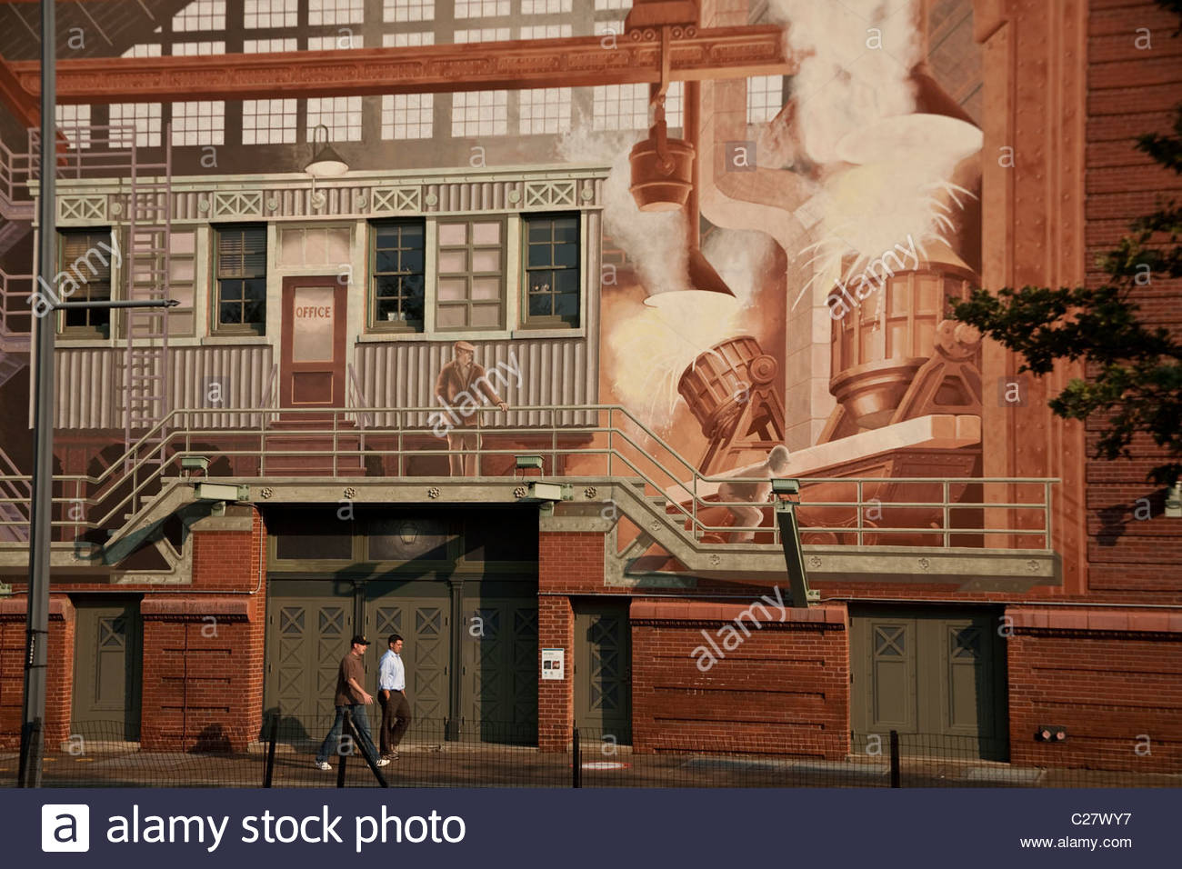 A mural painted on a brick building in the downtown business district. - Stock Image