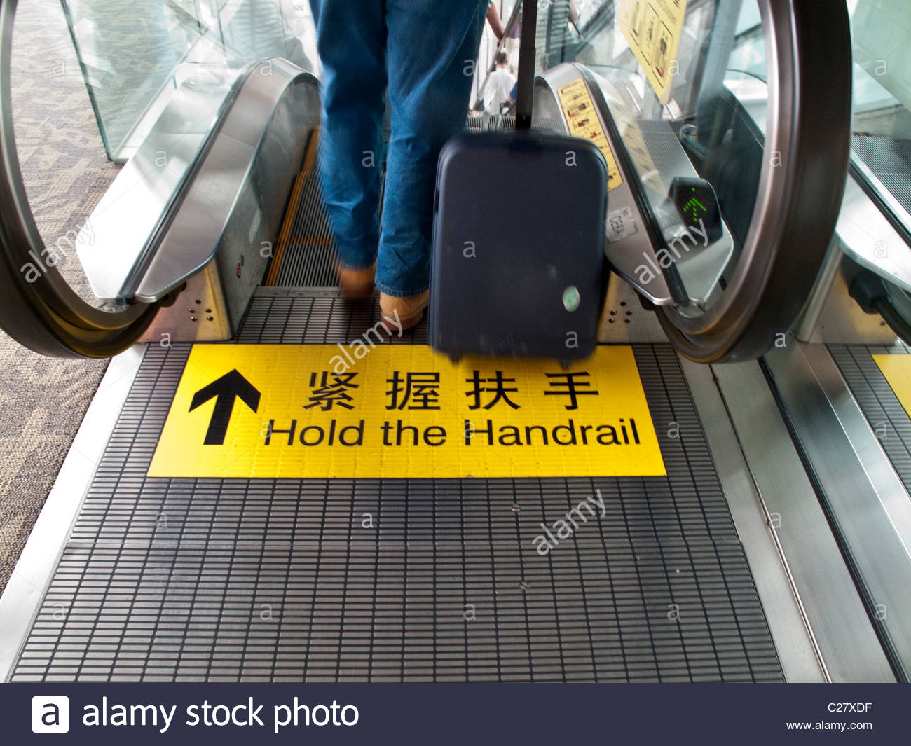 A 'hold the handrail' warning sign in English and Chinese. - Stock Image