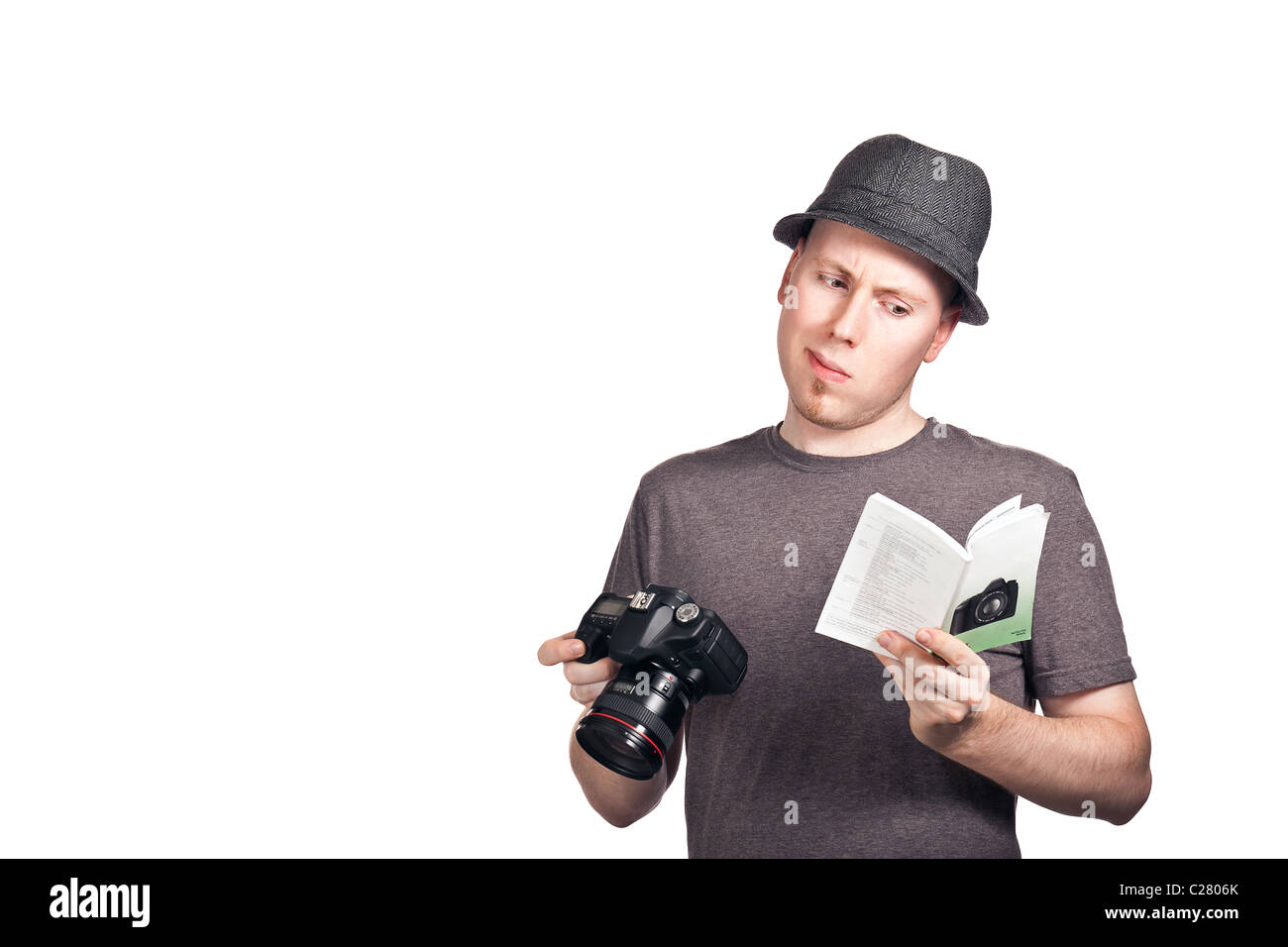 A young man looking confused reading an instruction manual for a DSLR camera. - Stock Image