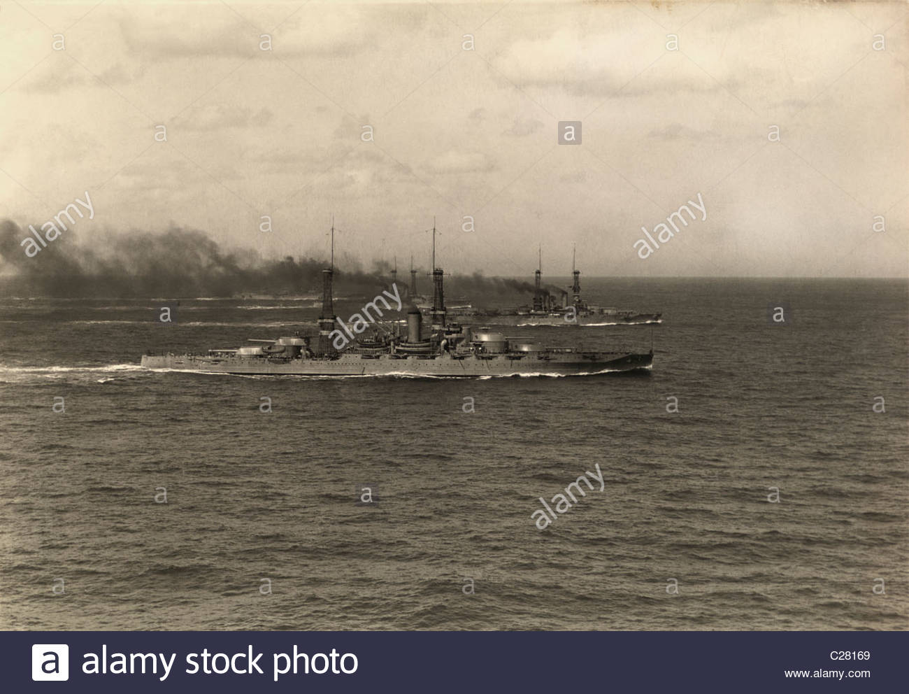 A fleet of United States Navy battleships practice maneuvers. - Stock Image
