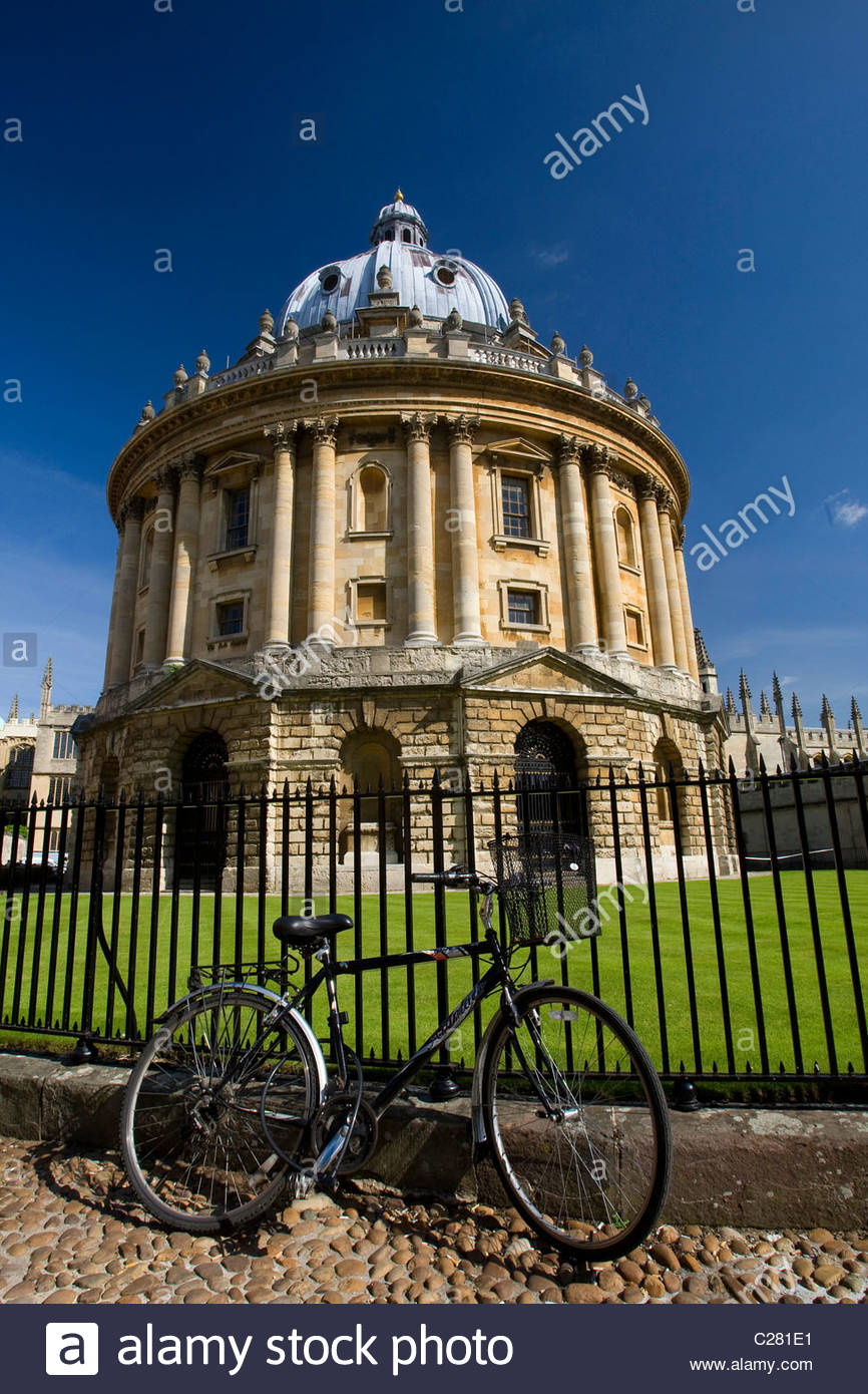 Bicycle outside a wrought iron fence around a round building. - Stock Image