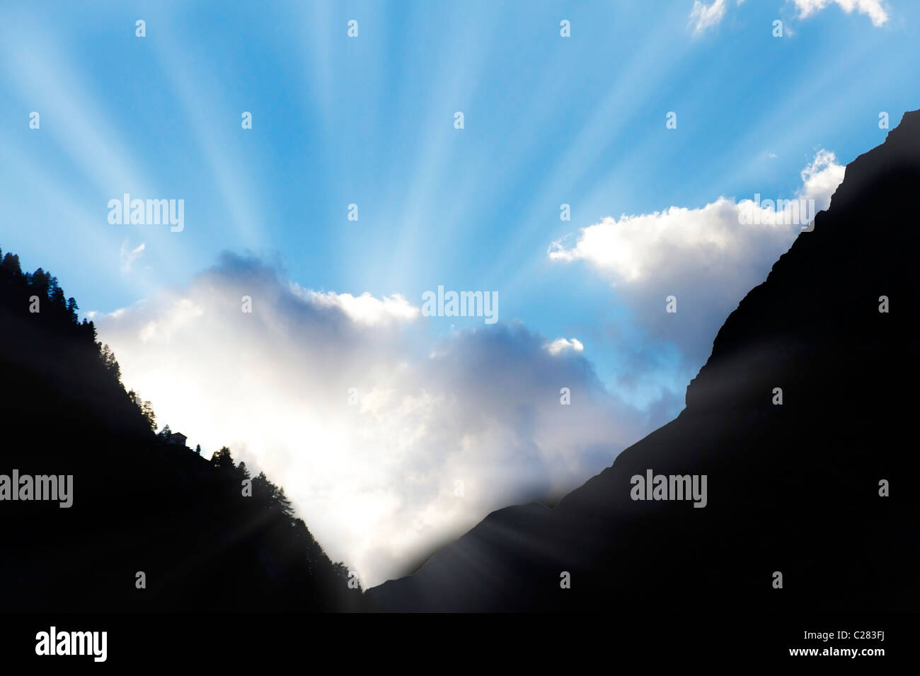sun bursts through clouds from a dark mountain valley symbol for hope,call not to give up,light at the end of the - Stock Image
