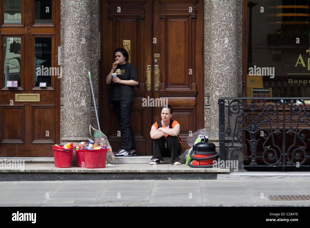 Office cleaners waiting outside office, Central London - Stock Image