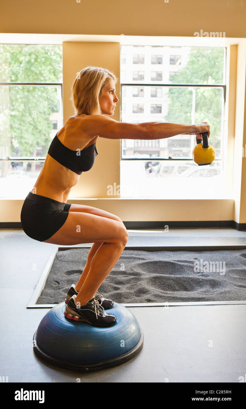 Physically fit woman holding a bent knee sit position while extending a kettlebell in front of her. - Stock Image