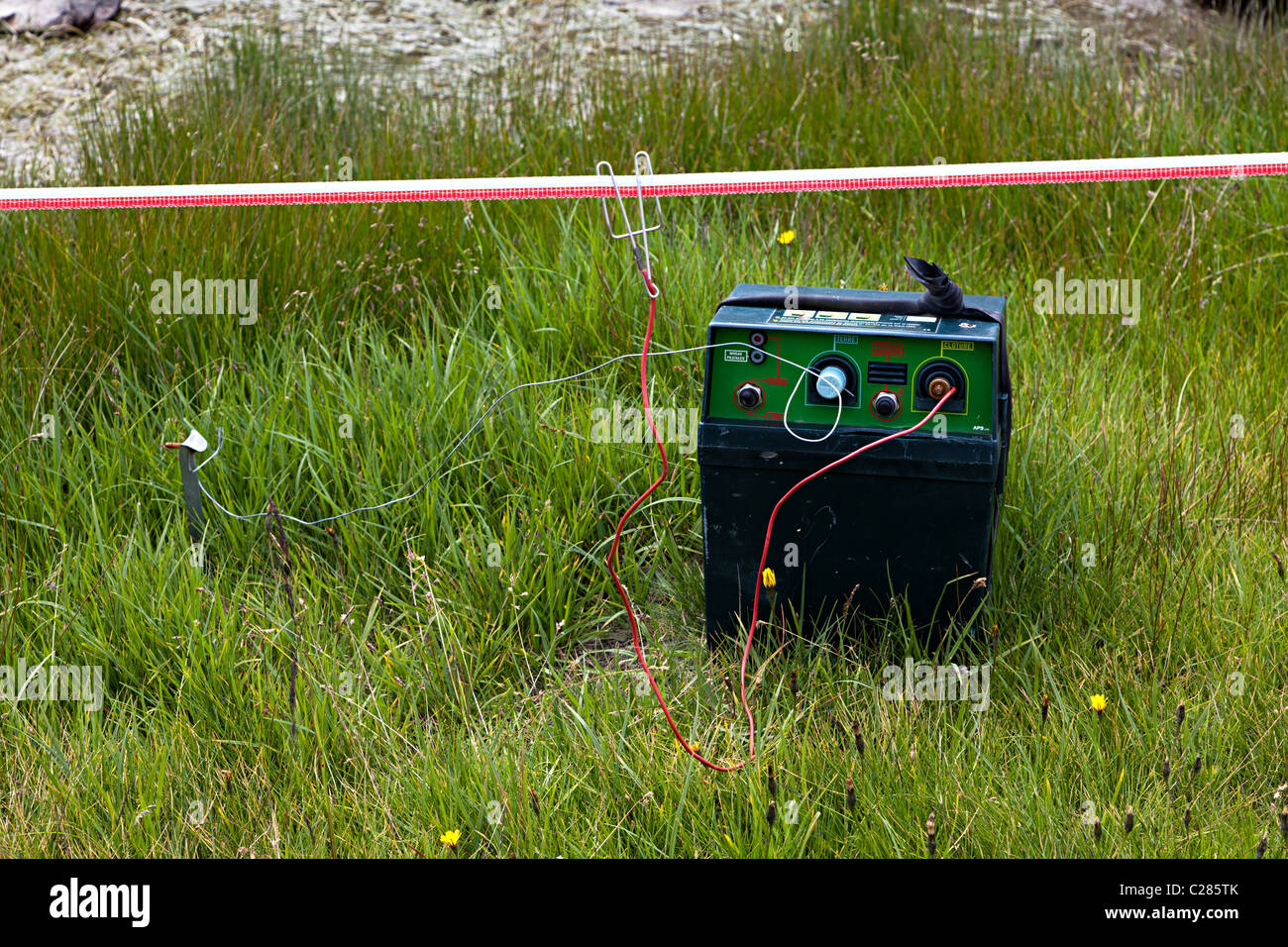 Electric fence to keep cattle out of nature reserve area with generator and earth spike to ground Arcalis Andorra - Stock Image