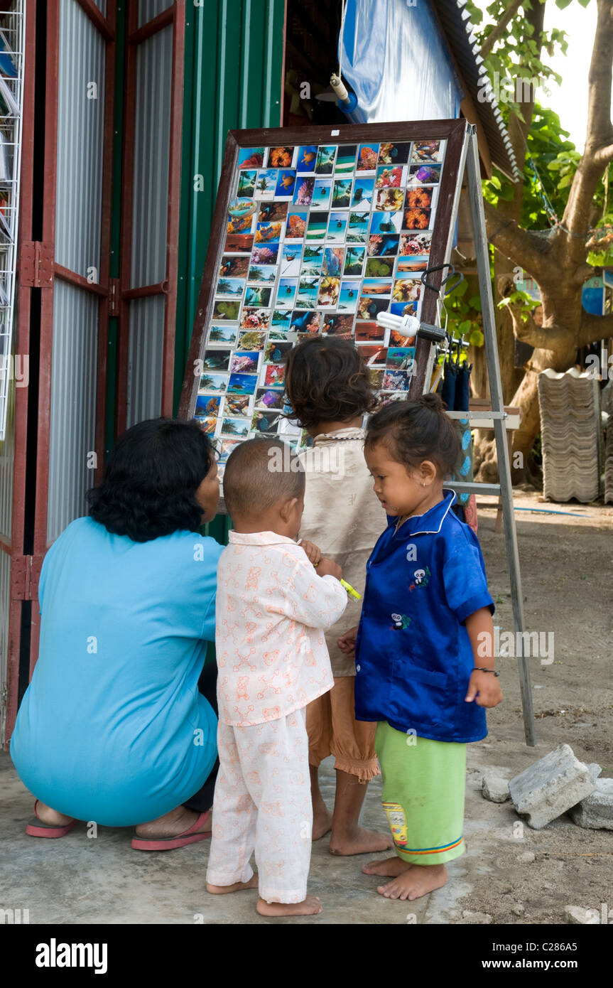 Children looking at a postcard rack, Koh Lipe, Thailand Stock Photo