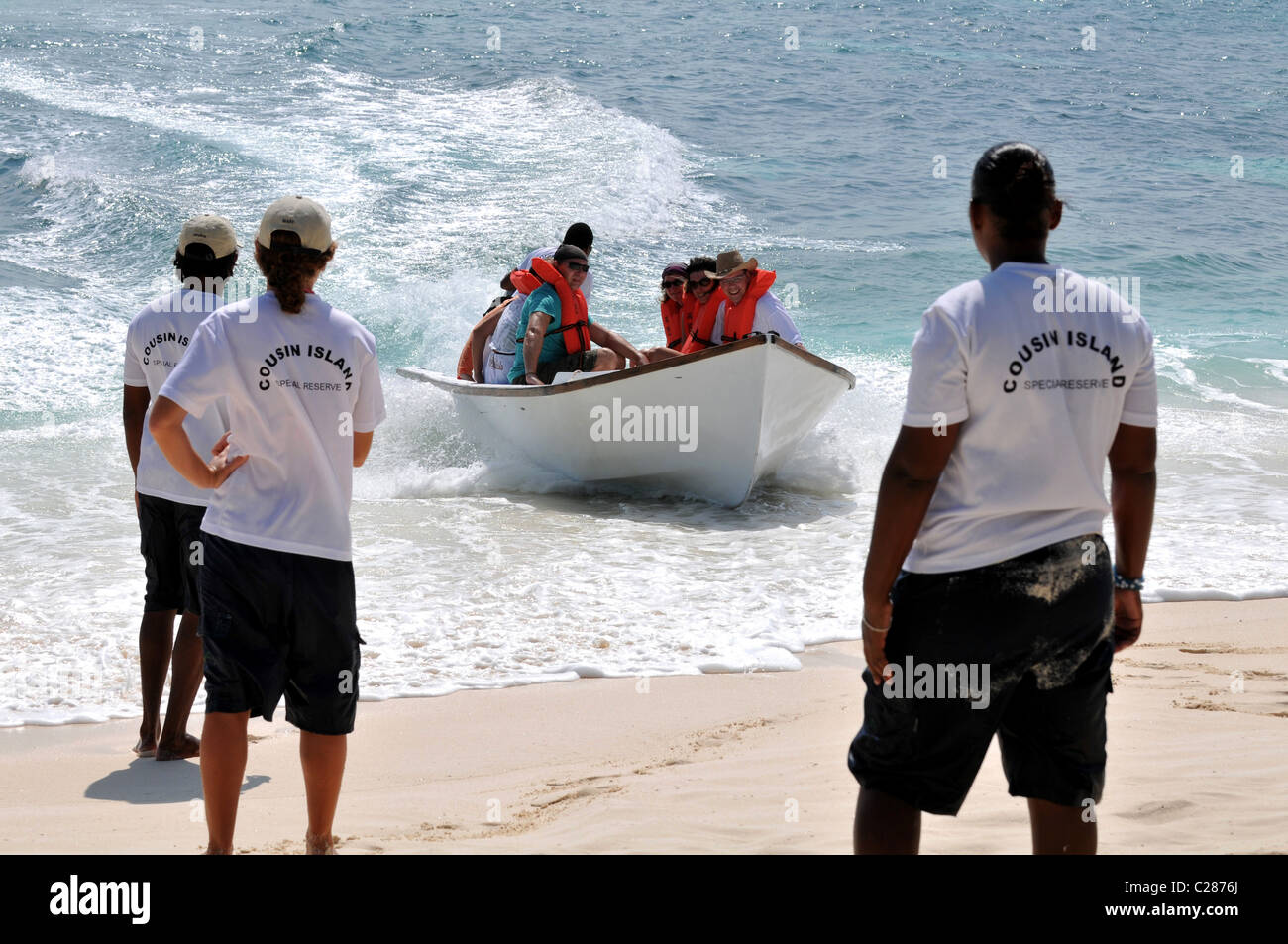 Fast arrival of tourist boat direct onto the beach at Cousin Island Seychelles. - Stock Image