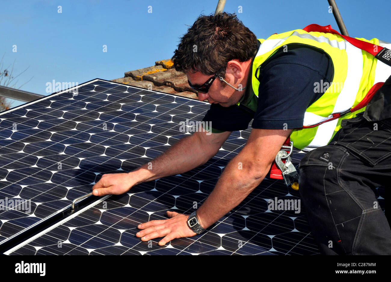 Solar panels being installed on a house roof, Britain, UK - Stock Image