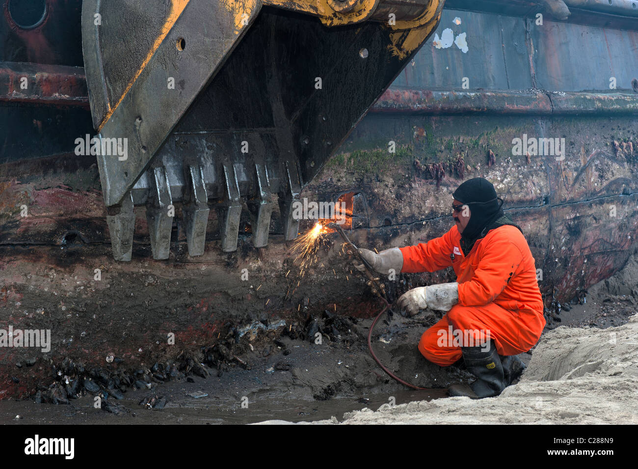 A worker is soldering off parts of a beached tug boat washed ashore and beached on East Beach, Santa Barbara, after - Stock Image