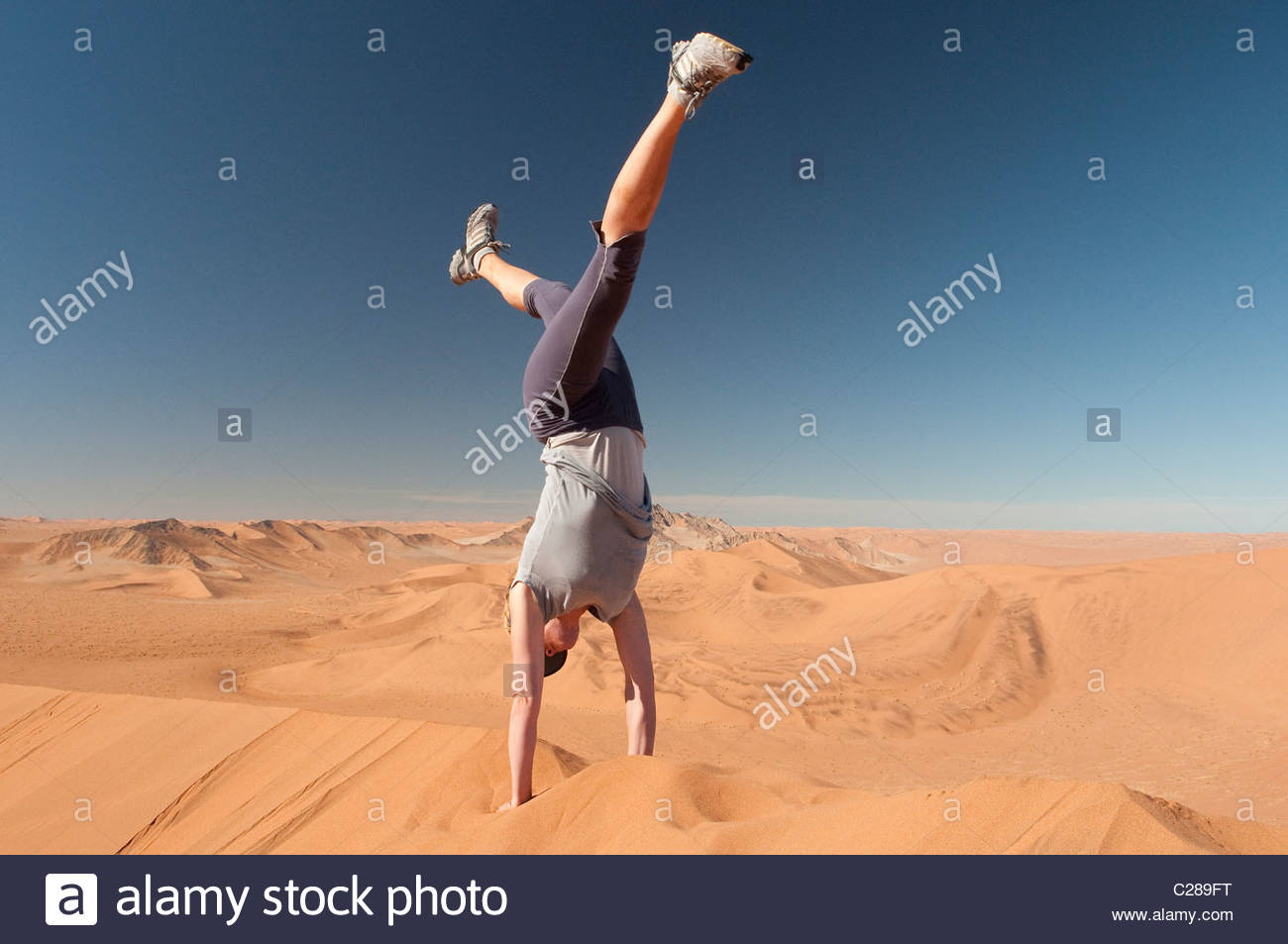 A woman does a hand stand on a sand dune in the Namib Desert, Namibia. Stock Photo