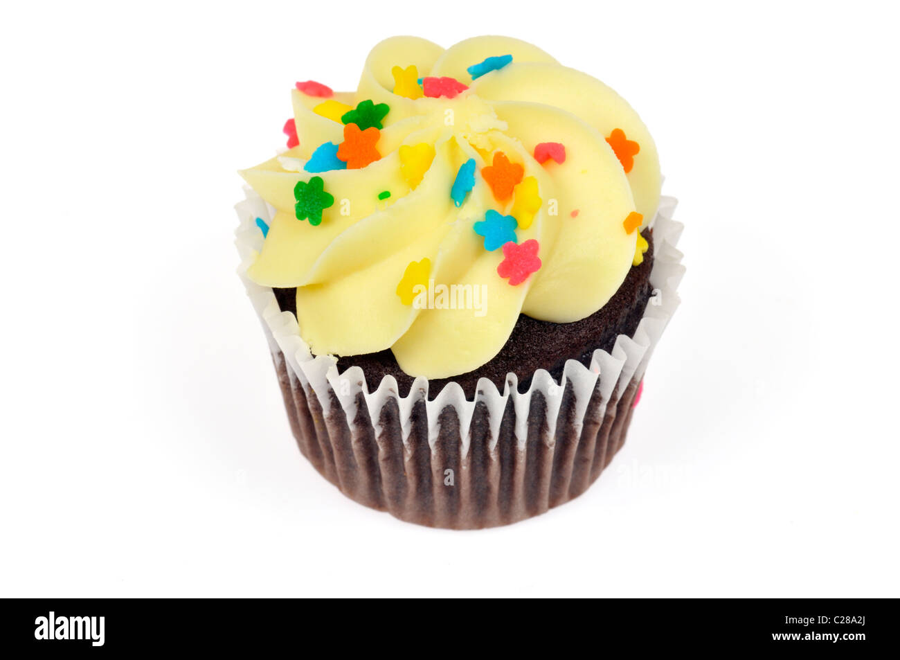 Chocolate cupcake decorated with yellow lemon icing and colorful sprinkles on white background cut out - Stock Image