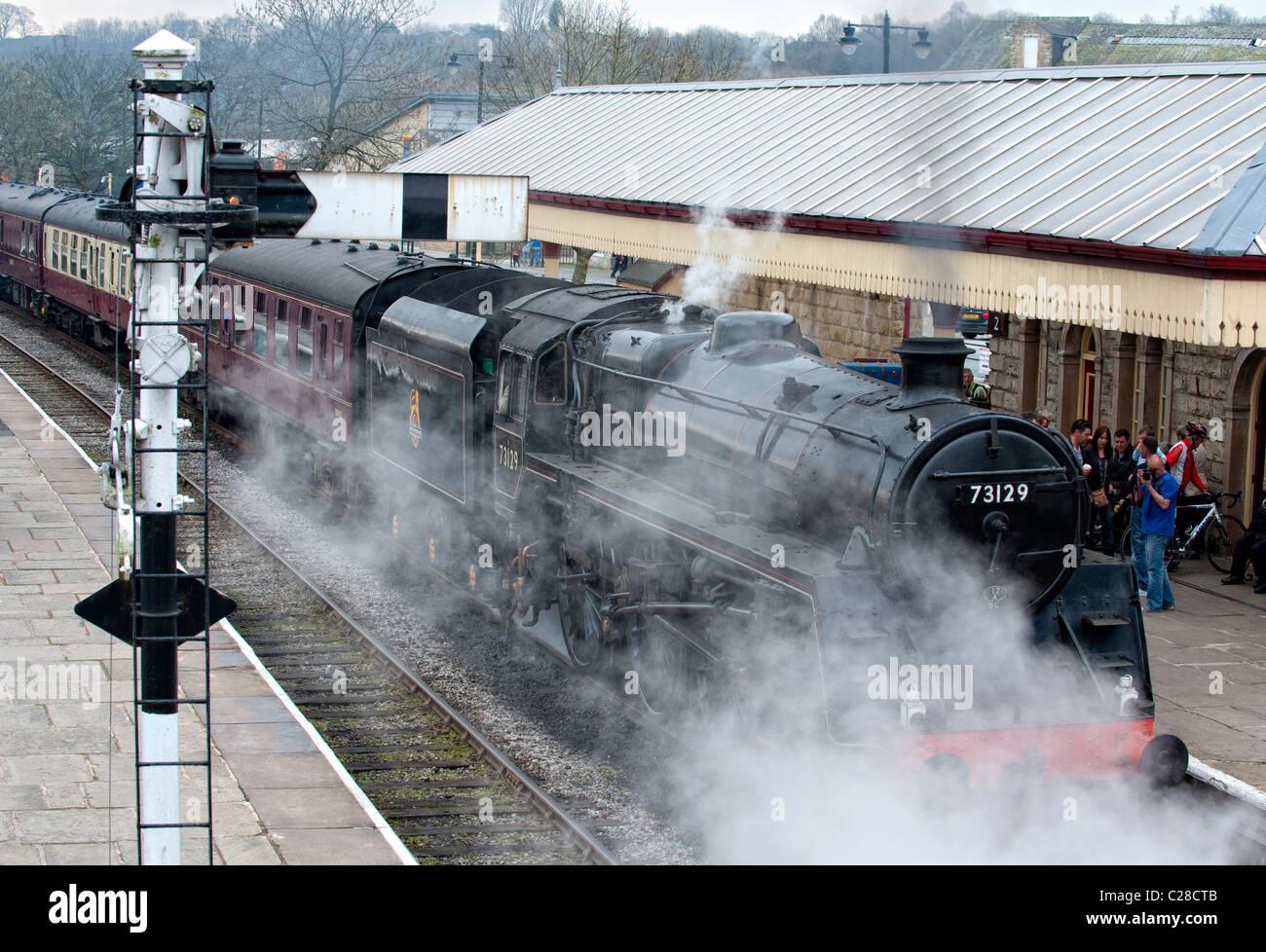 Steam locomotive pulls into the platform at Ramsbottom Station on the East Lancs Railway - Stock Image