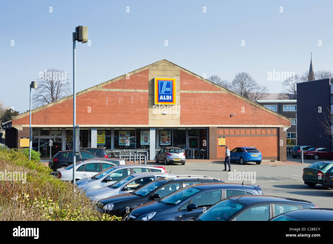 Aldi store front with cars in car park outside supermarket selling at cheaply. Bangor, Gwynedd, North Wales, UK, - Stock Image