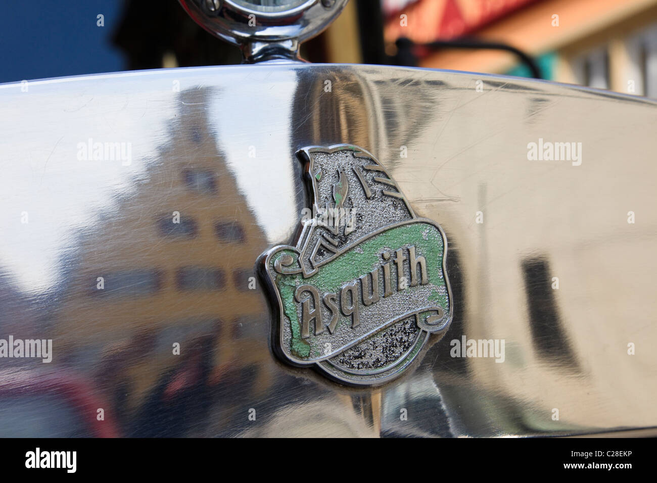 Maker's badge on the bonnet of an old Asquith vintage car with medieval buildings reflected in the chromework - Stock Image