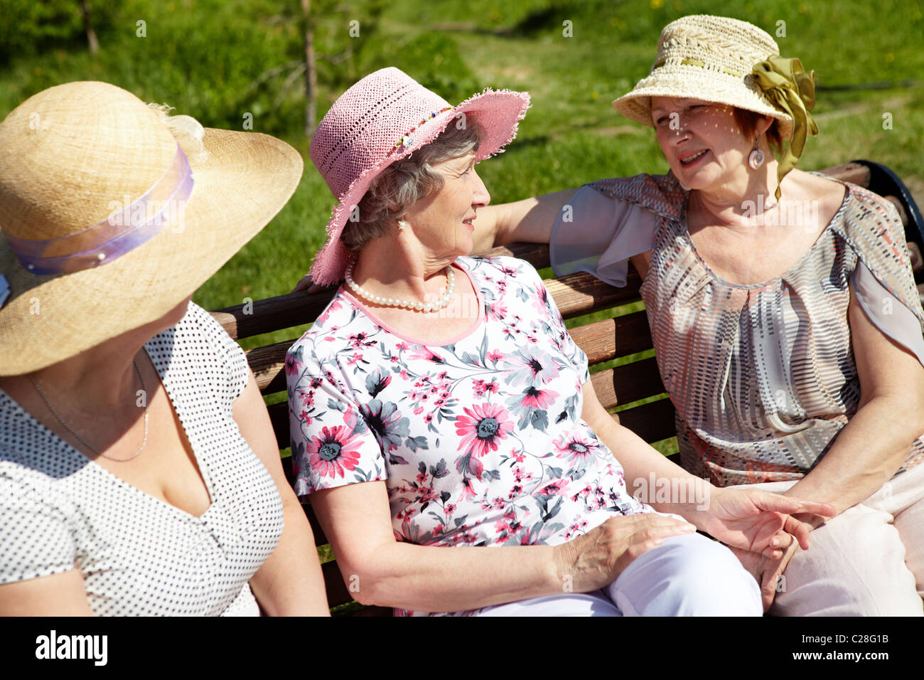 Portrait of senior women sitting on the bench in open air - Stock Image