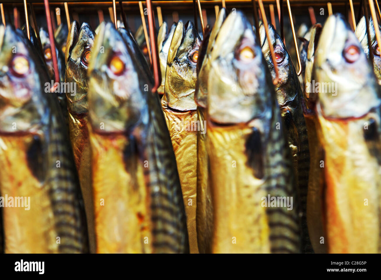 smoked kippers hanging in a smokehouse in Suffolk - Stock Image