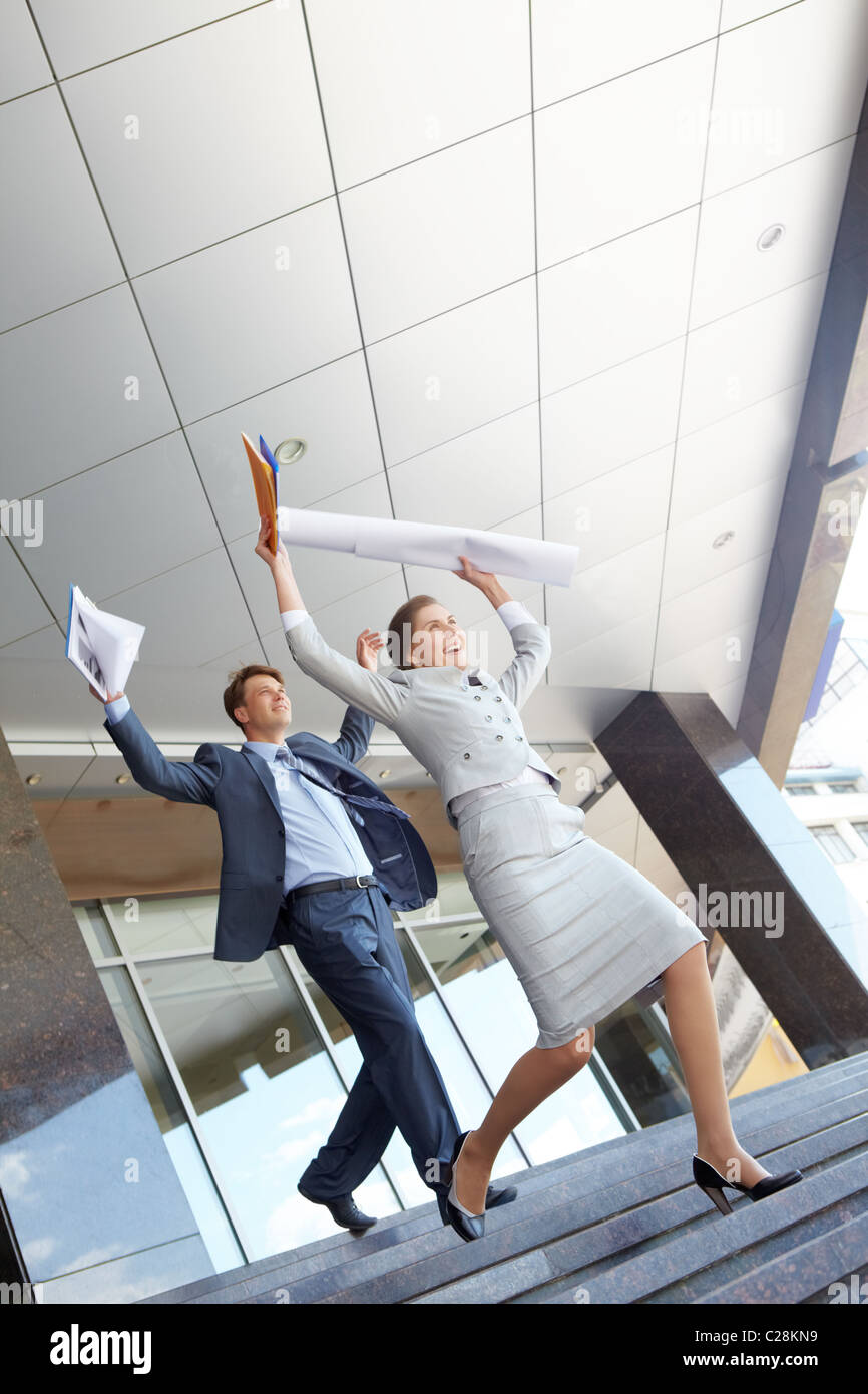 Successful businesswoman and businessman run down the stairs of the building - Stock Image